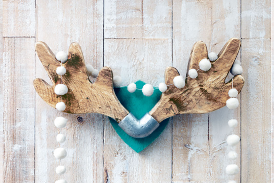 Upcycled antler-shaped coat rack mounted on a wooden wall, with a garland of festive white puffs hanging from it.