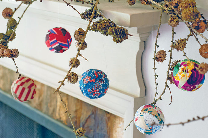 Handmade baubles covered in colourful fabric in a variety of colours, attached to a branch and set on a mantle.