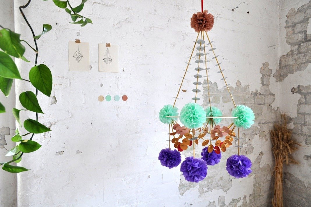 A pajaki chandelier with bright mint, purple and orange pompoms.