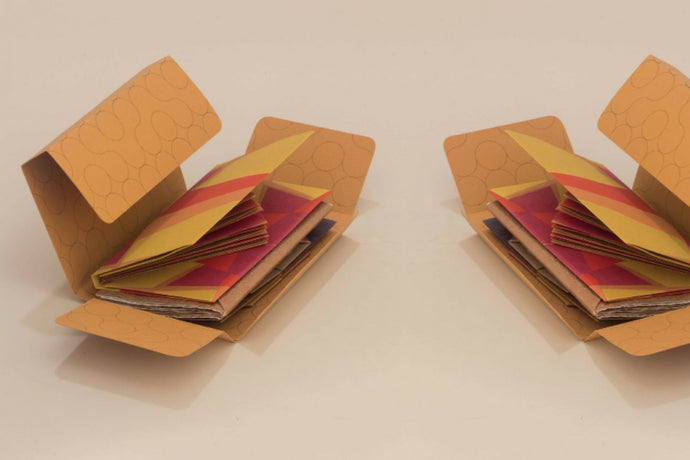 Two completed self-closing wrapper made of dark yellow paper with circle patterns, with a notebook placed inside.