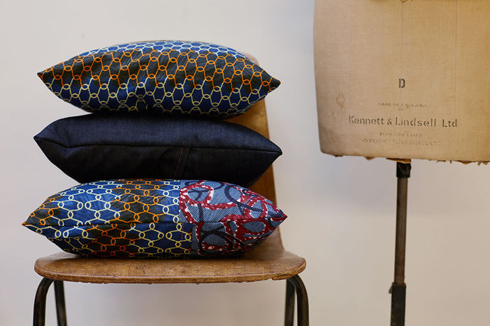 Three patterned cushions stacked on top of each other on a chair.
