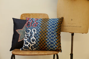 Two ornate square denim cushions posed on a chair.