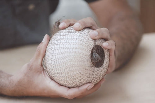 Detail of a ceramic bowl wrapped in mesh being held by two hands.
