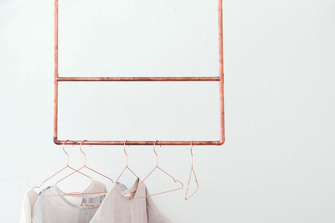 An upcycled copper-pipe clothing rail with copper hangers and white t-shirts hanging from it.
