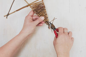 Detail of the process of creating a willow star: Julia cutting the excess willow from the point of a star.
