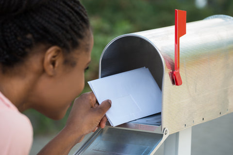 Woman Opening Her Mail Box To Retrieve Her Black Greeting Card