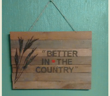 Pallet sign hanging on green wall