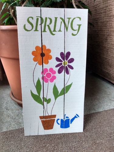 Spring-pallet sign on floor in front of pot