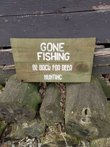 Gone fishing sign sitting on wood pile