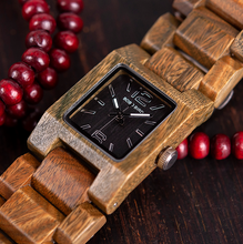 quartz wood watch laying on red beads