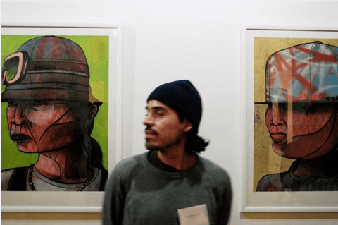 Nelson Rivas standing next to two art pieces