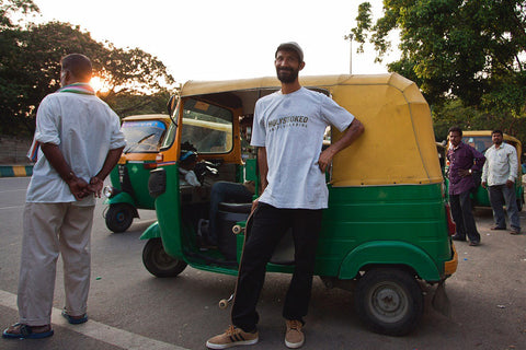 Sommana, an OG skater from Bangalore, holding a Holystoked skateboard, next to an autorickshaw.