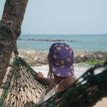 Surfer girl sitting on a hammock and looking at the sea, while wearing the Gokarna Hat. This is a collaboration with Holystoked India.