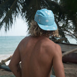 Rear shot of the Dwarka Hat by Alwards, worn by a surfer.