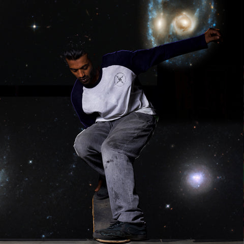 Product shot of the Poser Navy t-shirt. with a space-like background, while the skater nails his trick.