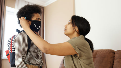 mother puts reusable custom face mask on son