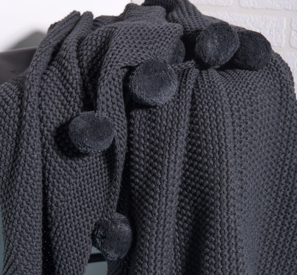 Charcoal decorative blanket with pompoms by Déniché Boutique