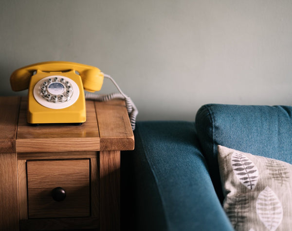 Old yellow telephone on top of a wooden side table that is beside a blue couch with a grey pillow on top.