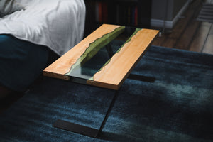 Handmade river coffee table with a big leaf maple top, river glass centre, and asymmetric black powder coated steel legs