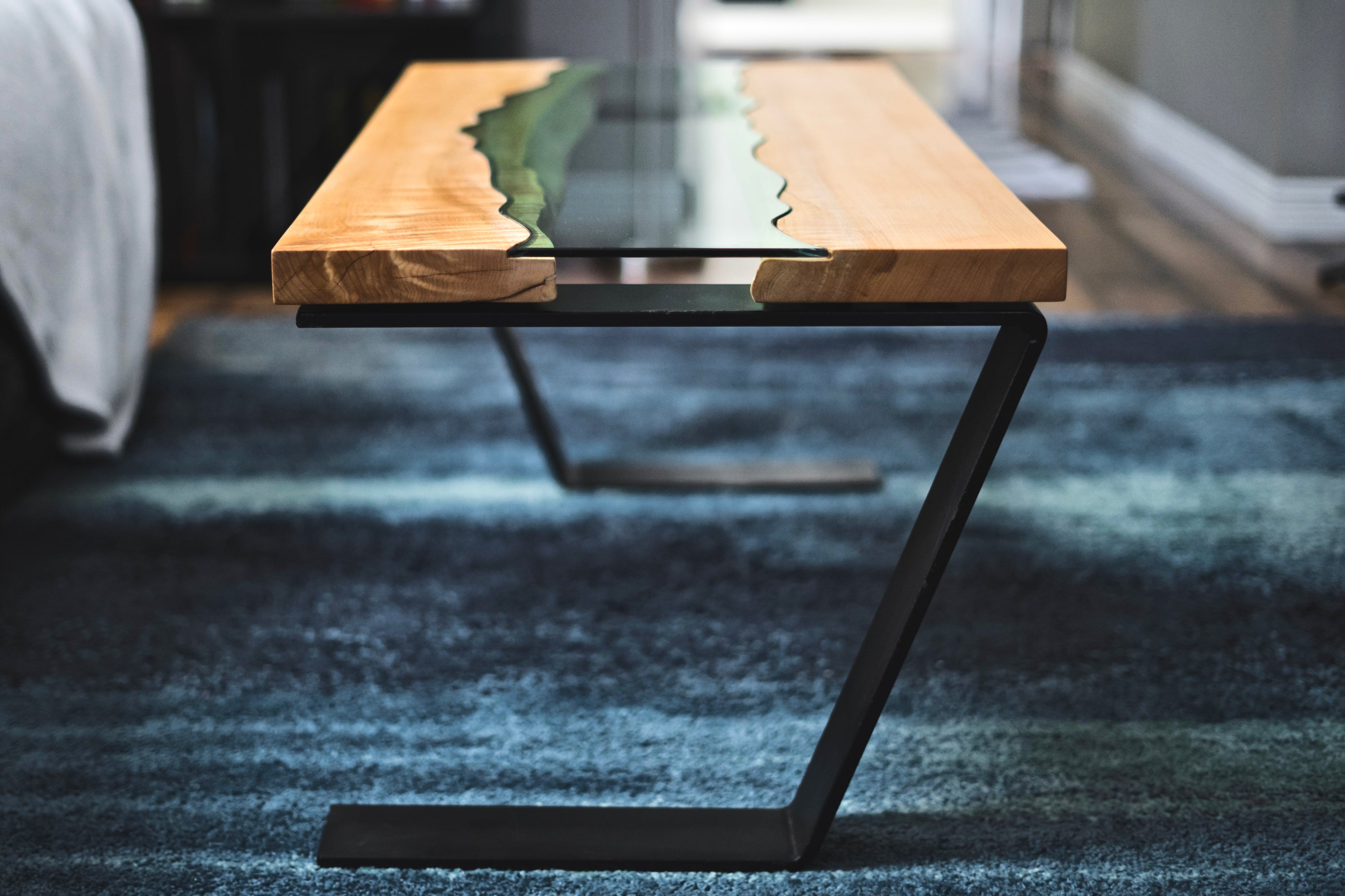 Handmade river coffee table with a big leaf maple top, river glass centre, and asymmetric black powder coated steel legs.