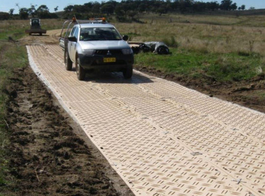Truck driving over duradeck ground protection mats on jobsite