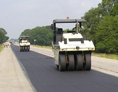 Pavers going over petromat during road construction