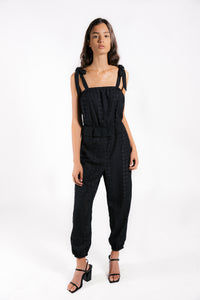 Lenon Collection. Peplum sleeveless jumpsuit. Black embroidered eyelet with adjustable tie straps.