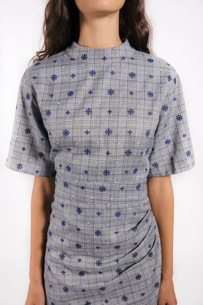 Lenon Collection. Grey/ navy plaid embroidered print with mini ruffle hemline. Mock neck and short sleeves.