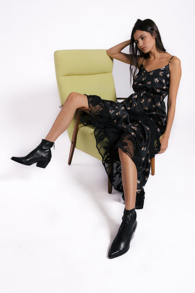 Lenon Collection. Satin crepe maxi dress in a black wild flower print. Adjustable straps, lace panels throughout the legs.