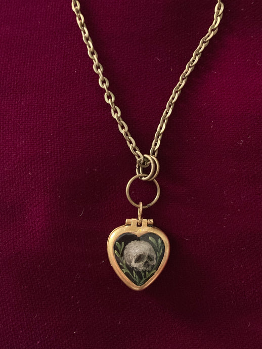 A thumb-nail sized heart-shaped brass pendant. The front is painting is a tiny human skull. One each side of the skull are small branches with leaves. The background is black.
