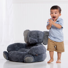 Kid standing next to Elephant Chair