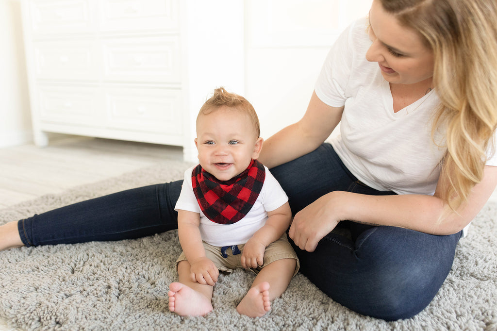 Baby wearing black and red buffalo check bib and sitting on the floor with their mother smiling