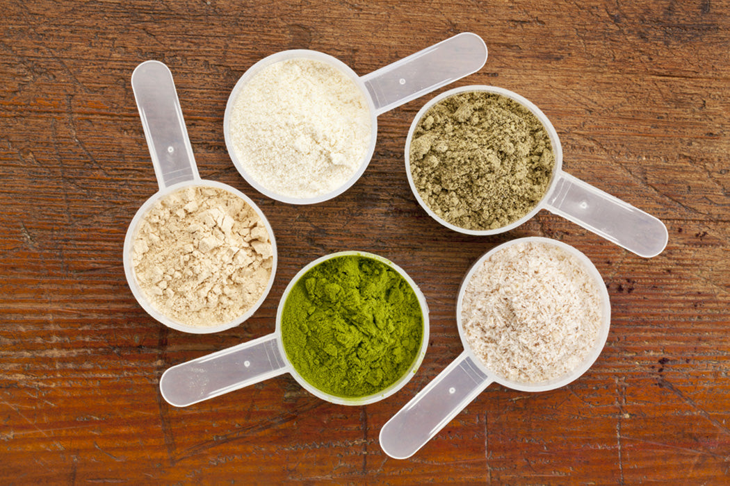 five plastic measuring cups of different superfood supplement powders