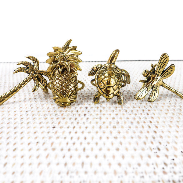 This is the collection of hand made brass napkin rings.  The Palm Tree, The Pineapple, The  Turtle and The Fire Fly.