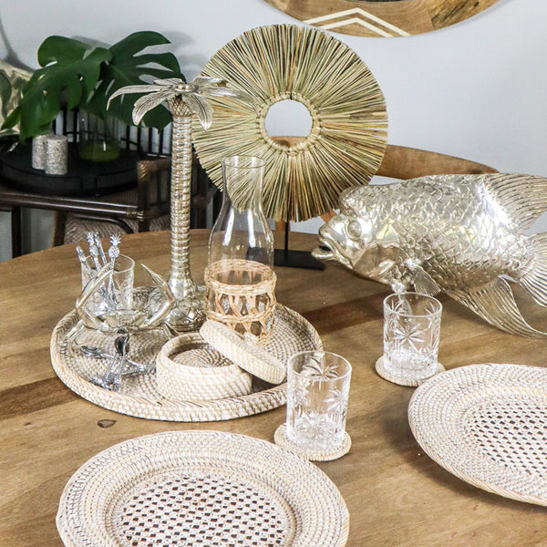 What have we here in this photo?  I can see Sea Grass Table Art, Silver Candlesticks, Silver Groper Fish, Rattan Boxed Coasters, Silver Crab, Silver teaspoons, flat round whitewashed rattan tray and round whitewashed table chargers.