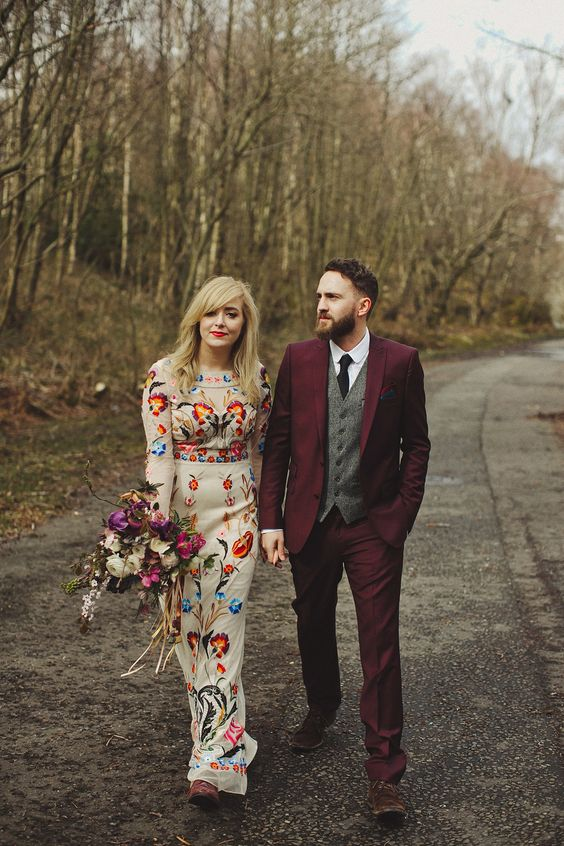 Bride in unique embroidered wedding dress and groom in burgundy suit