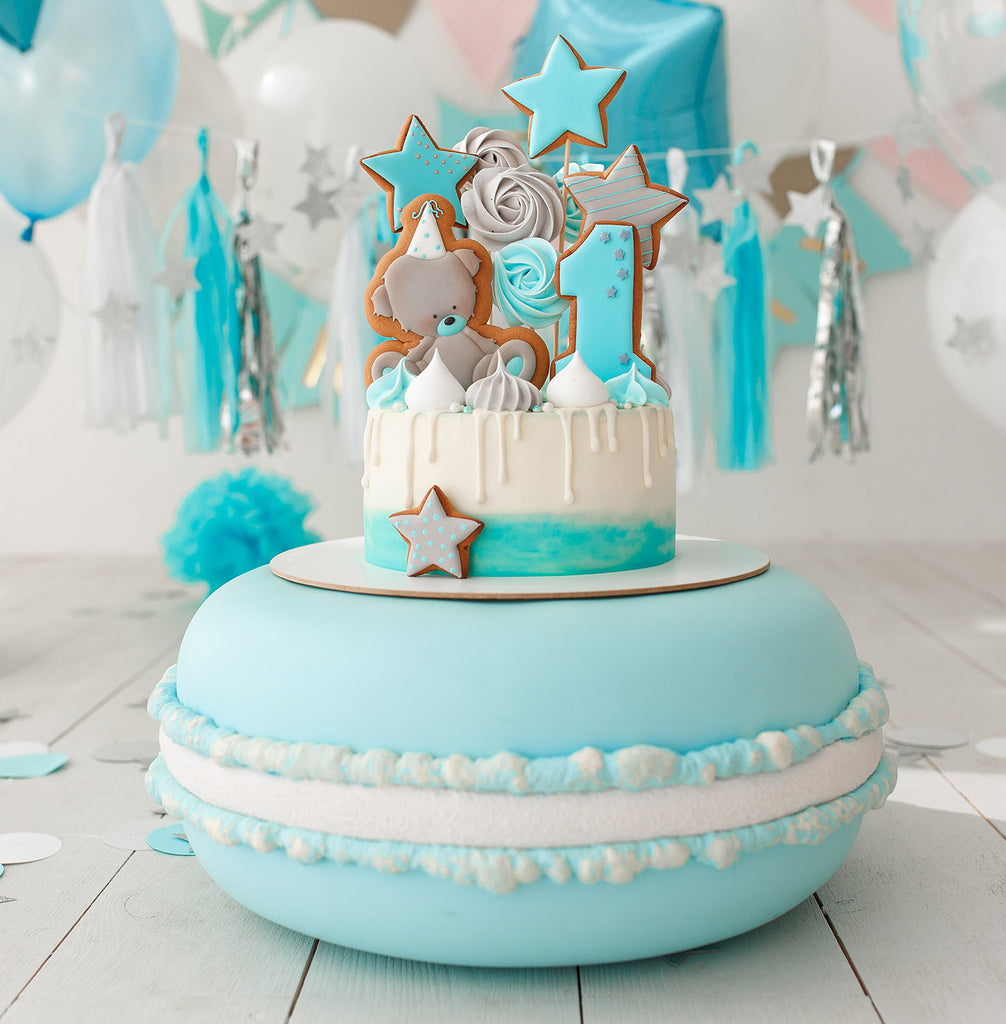 A blue macaroon inspired cake covered in fondant icing and decorated with shapes and numbers made out of iced biscuits