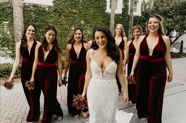 twobirds bridesmaids in burgundy velvet convertible jumpsuits