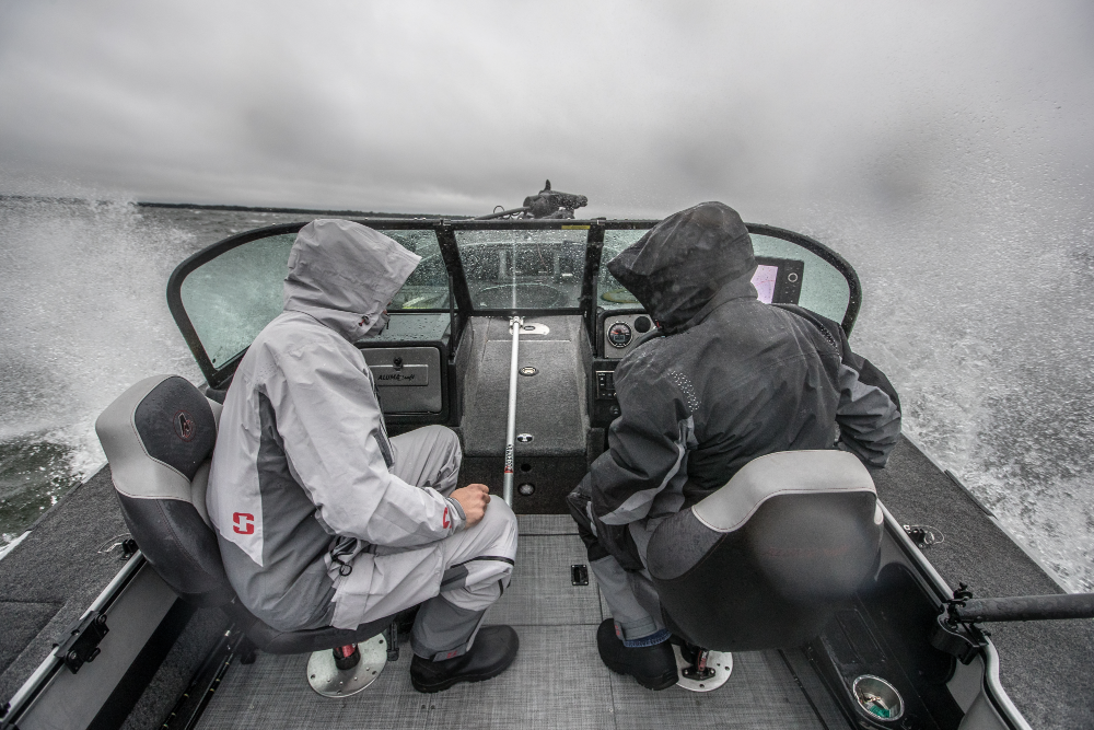 Lifestyle Image of Two Men Driving Boat in Rain and Waves Wearing Striker eVolve Rain Suits