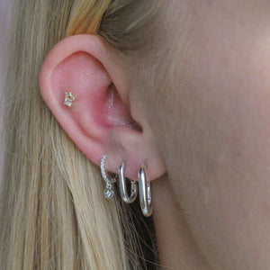 Crystal Disc Huggies in Silver worn in third lobe piercing
