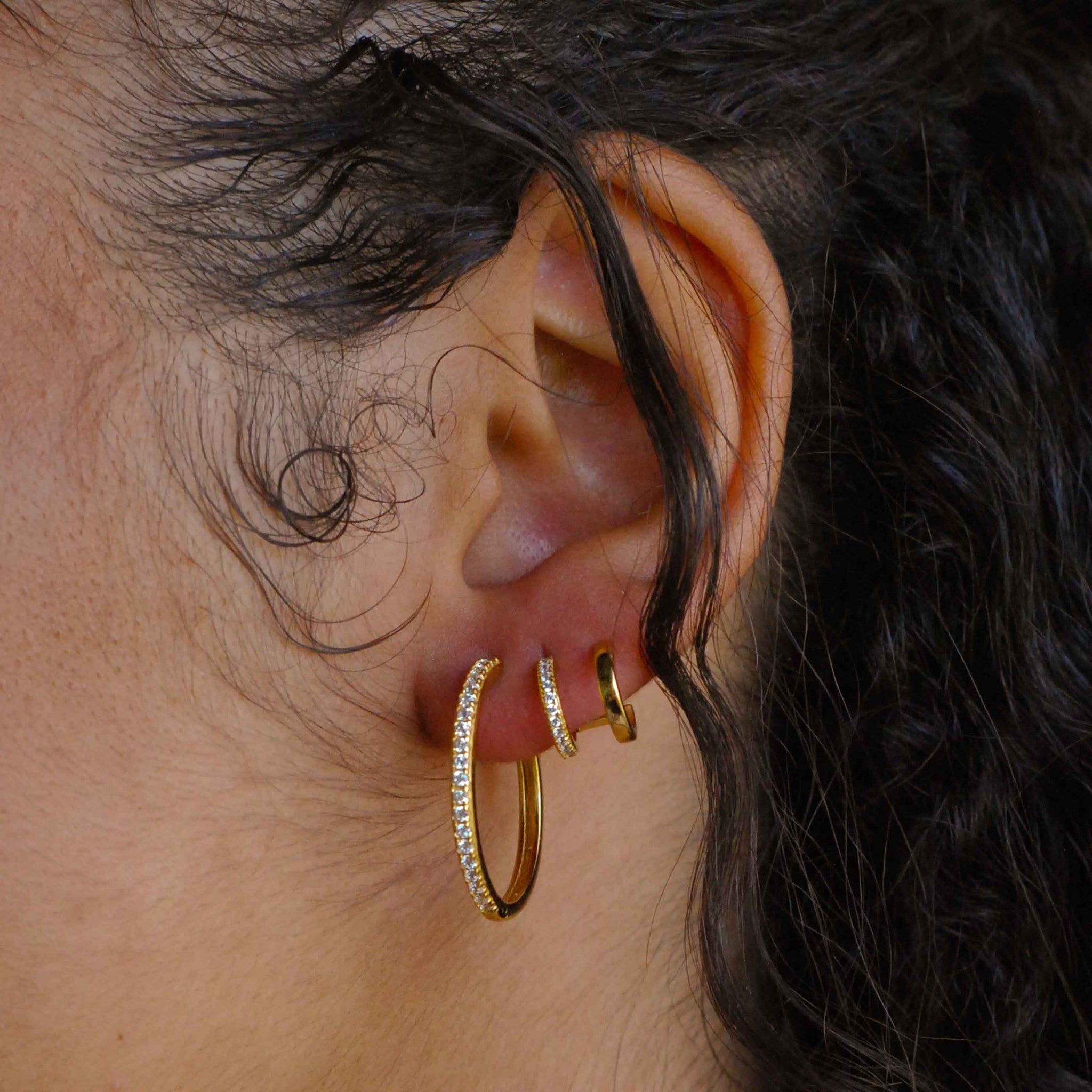 Crystal Hinge Hoops in Gold worn with illusion stud earrings in gold