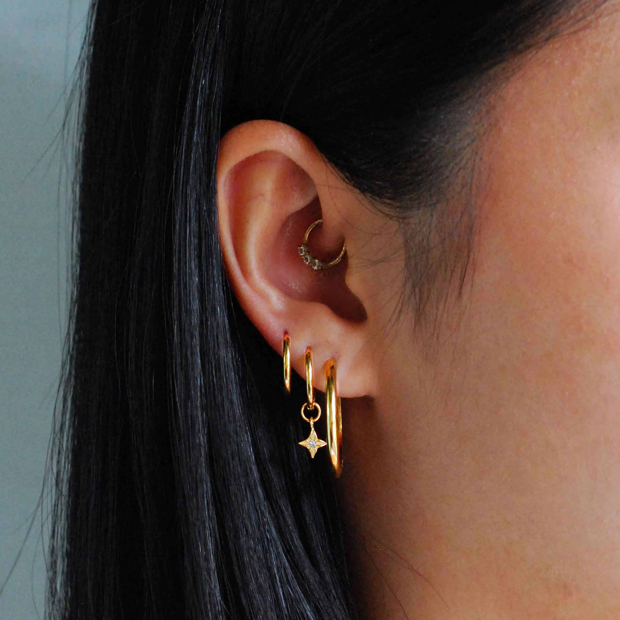 Etched Star Hoops in Gold worn with simple hinge hoops