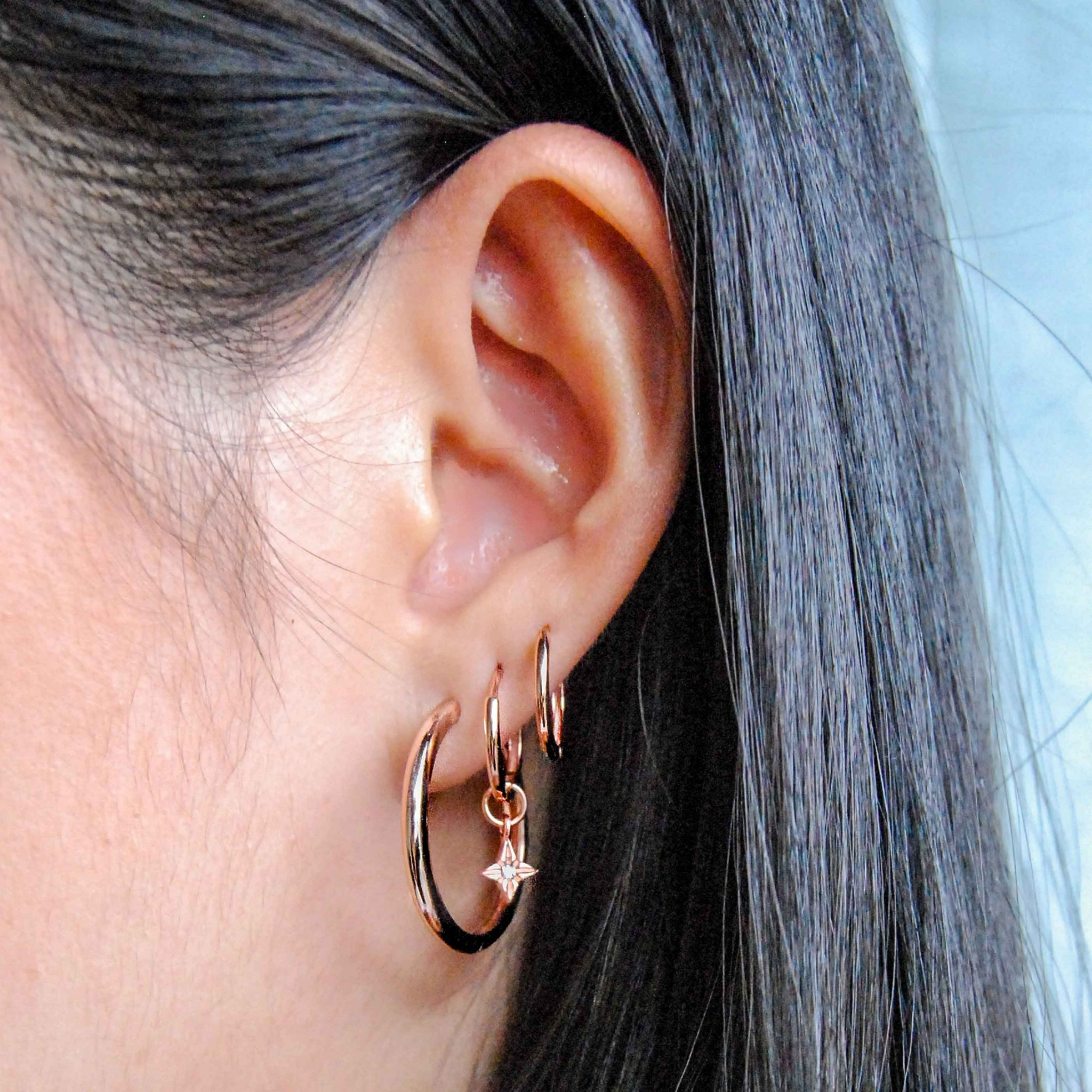 Etched Star Hoops in Rose Gold worn with simple hinge hoops in rose gold
