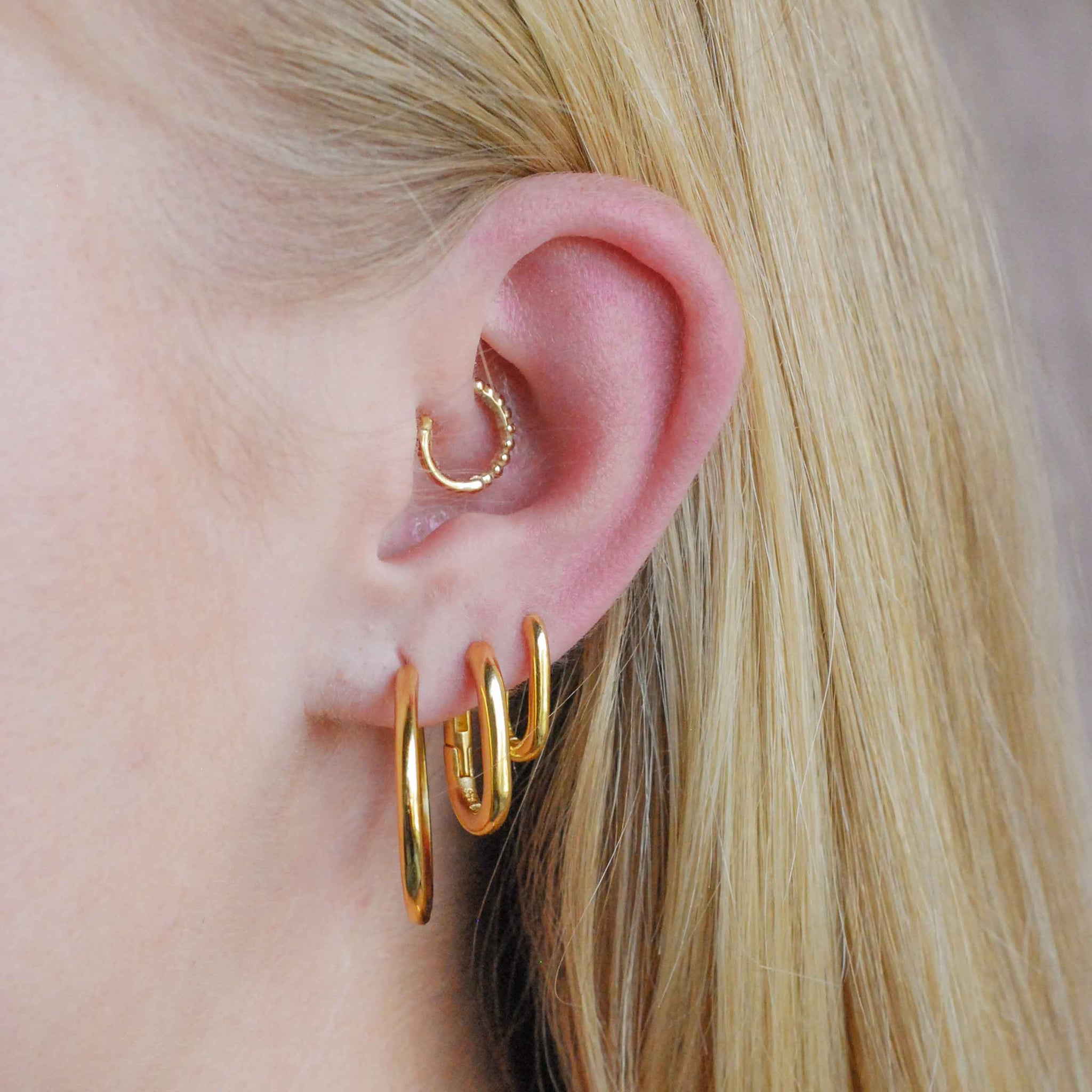 Simple Hinge Hoops in Gold worn with rectangular hoops and huggies