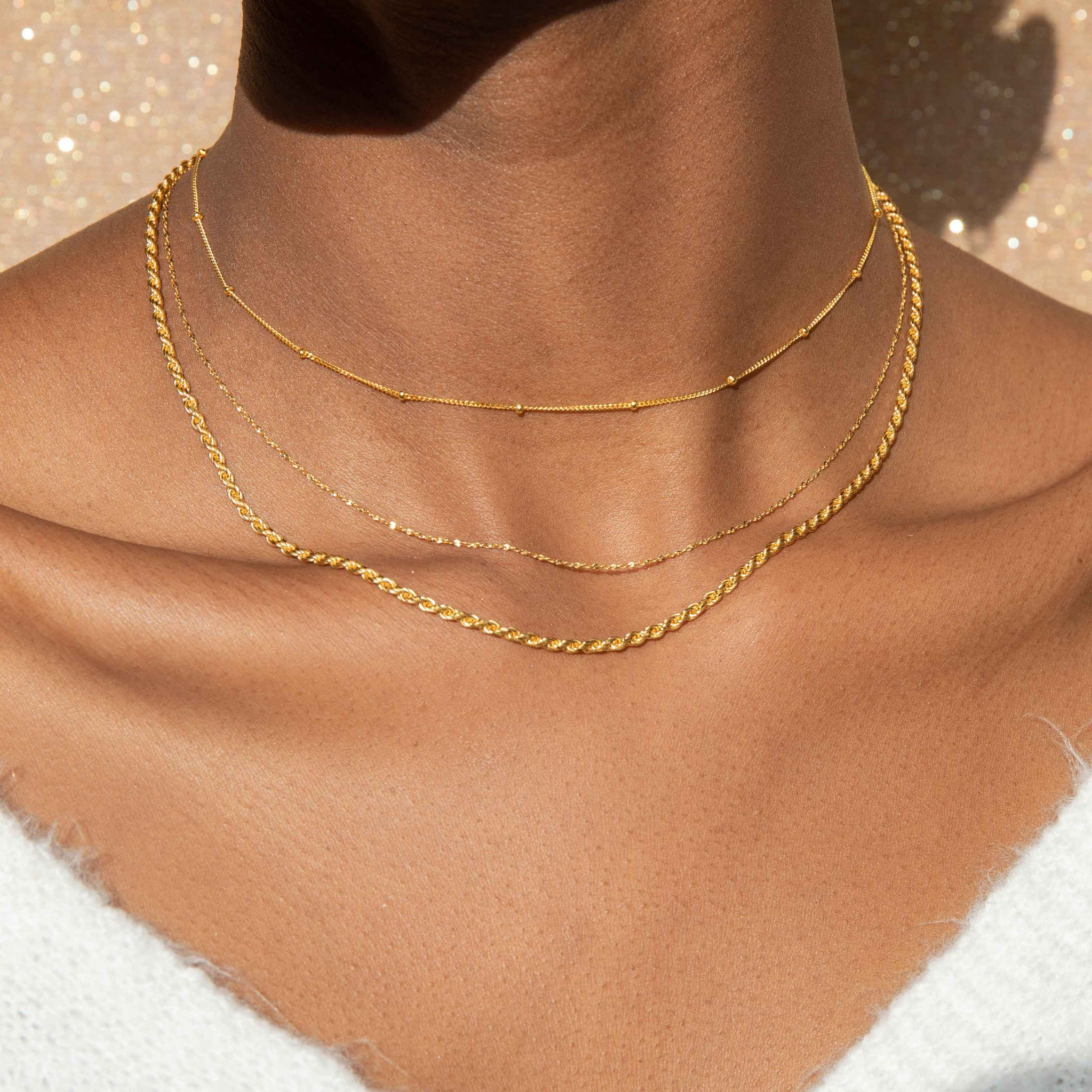 Basic Small Beaded Choker in Gold worn with chain necklaces