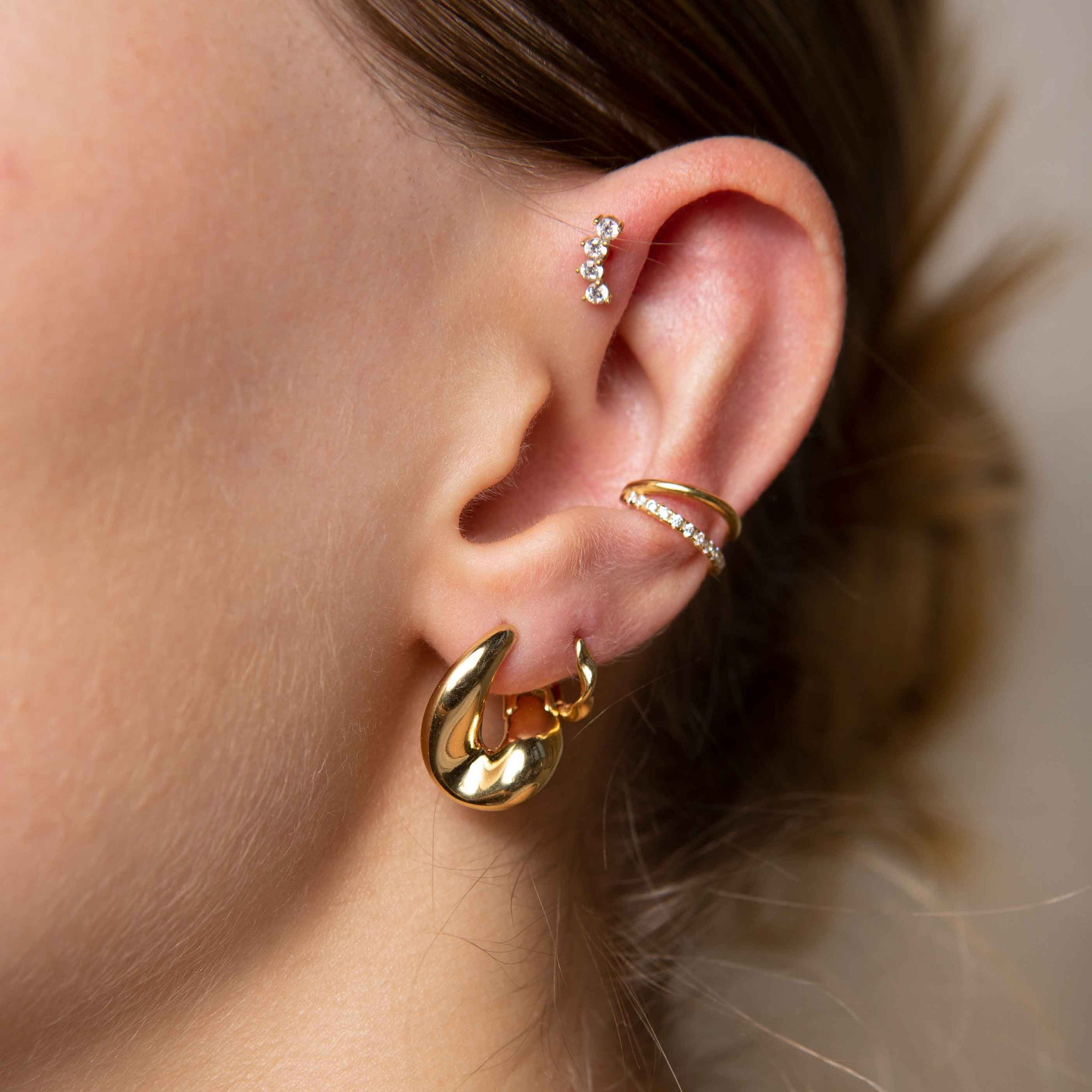 Curved Crystal Barbell in Gold worn with gold ear cuff and gold chunky hoops