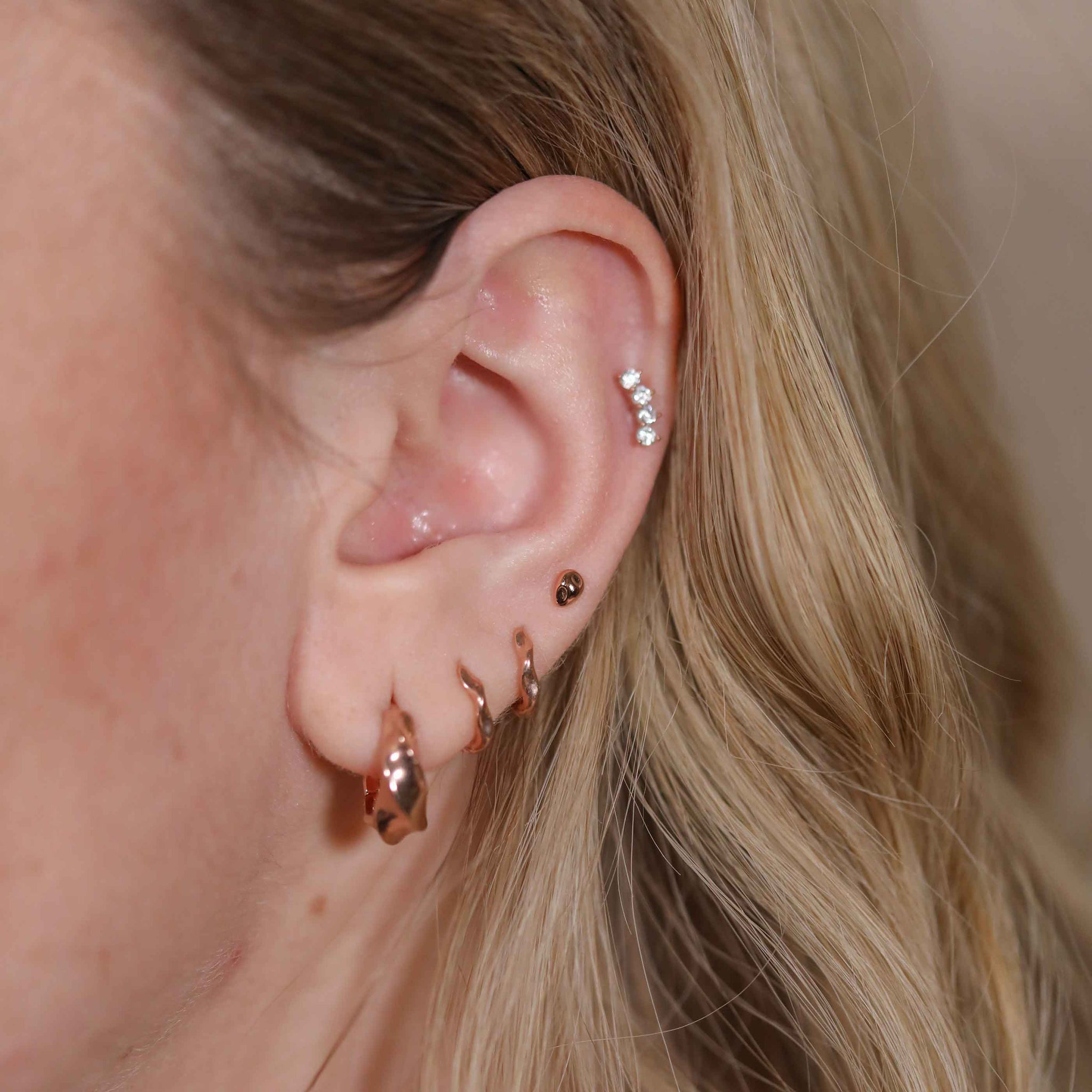 Molten Stud Earrings in Rose Gold worn with curved crystal barbell and elemental huggies