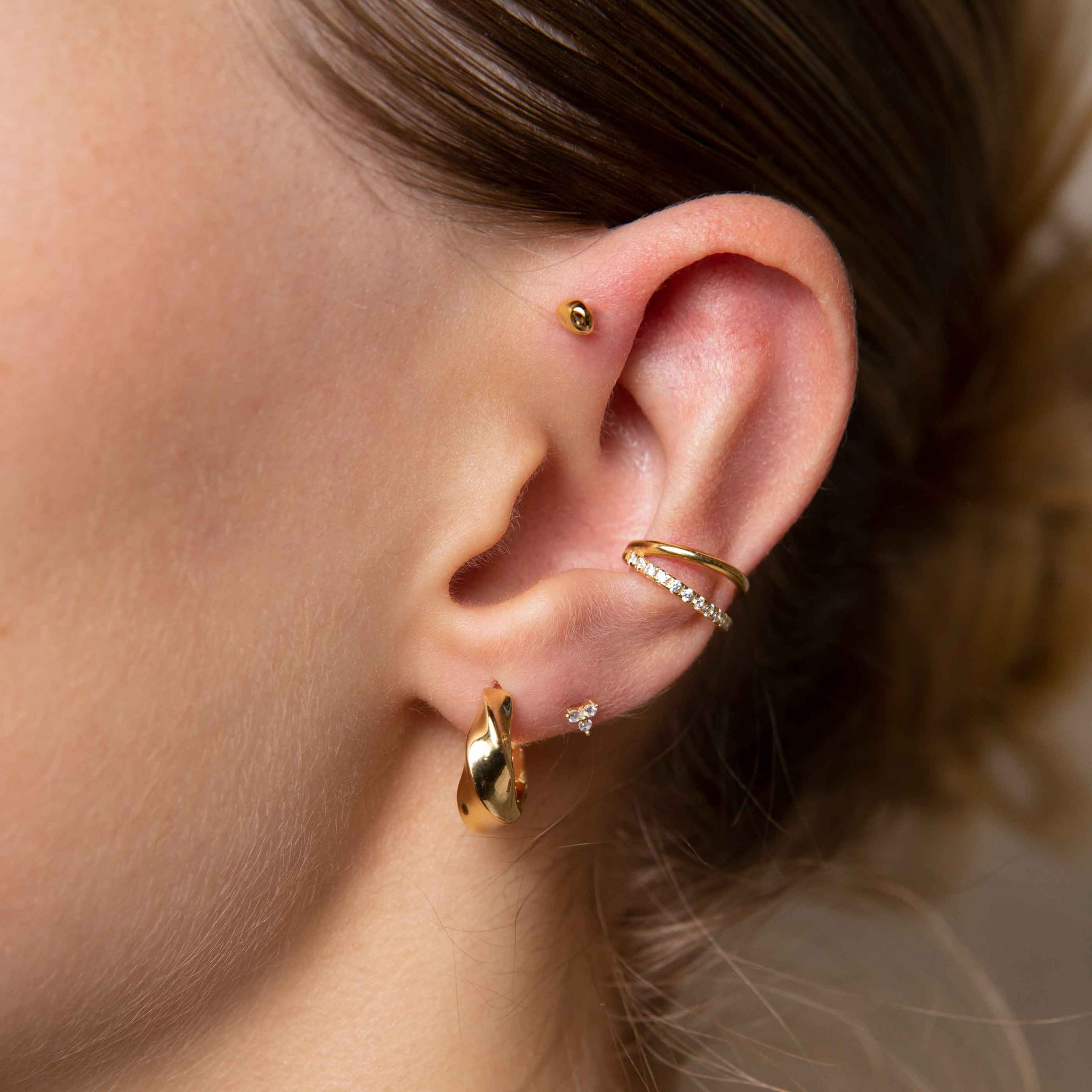 Triple Crystal Stud Earrings in Gold worn with elemental hoops