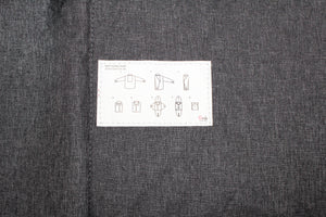 Dark gray fabric with a white tag fully sewn down with printed visual step by step instructions on how to fold shirts correctly to fit into the Shirts/Pants Folder.