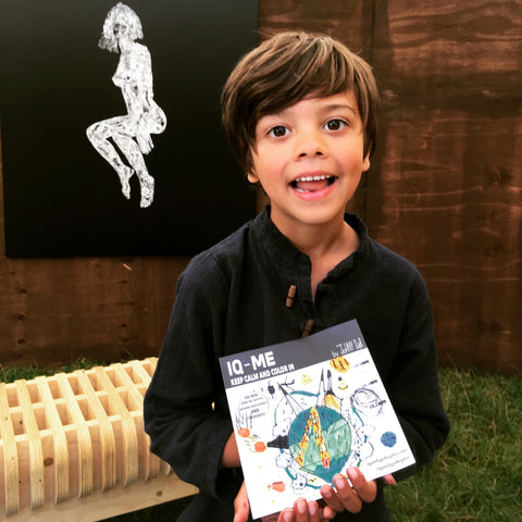 Smiling boy with IQ-ME colouring book and art piece at a summer festival